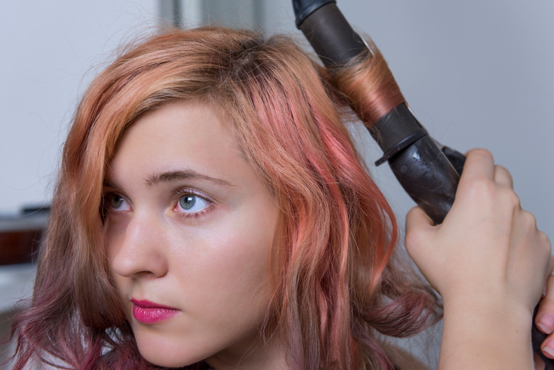 Young woman using curling iron on hair - babylissPRO reviews