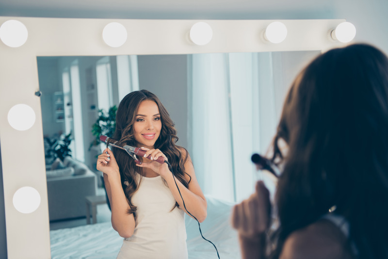 Woman curling hair with a 1 inch curling iron